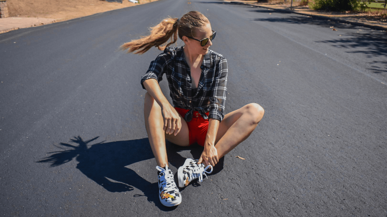 Donna Gail sitting on newly paved asphalt wearing a Pixar Cars inspired outfit - a black and white plaid shirt tied up, a pair of high waisted red shorts, and Lightning McQueen shoes. Picture taking during mid-hair flip