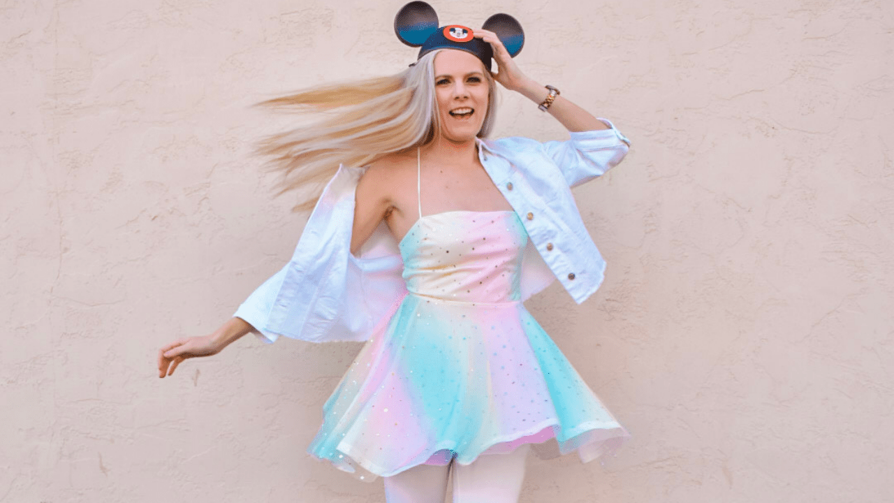 I am wearing a white denim jacket, a sparkly pastel rainbow dress, and a pair of Mouseketeer ears. I am spinning so my dress is twirling and my hair is flipped out to the side.